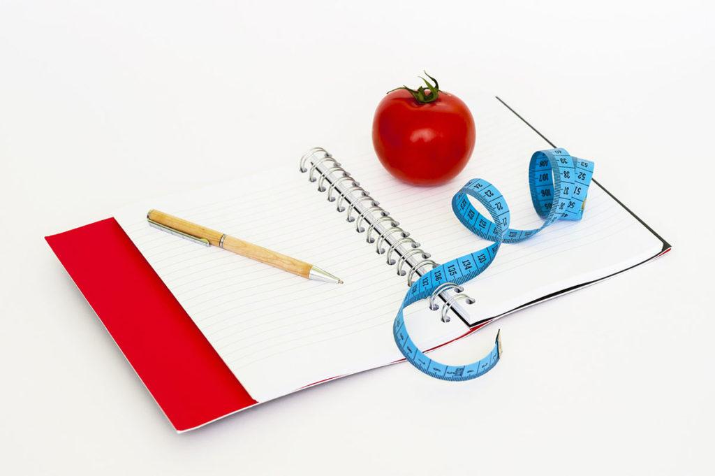 Block, Stift, Apfel und Maßband