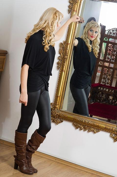 Junge Frau steht vor dem Spiegel
