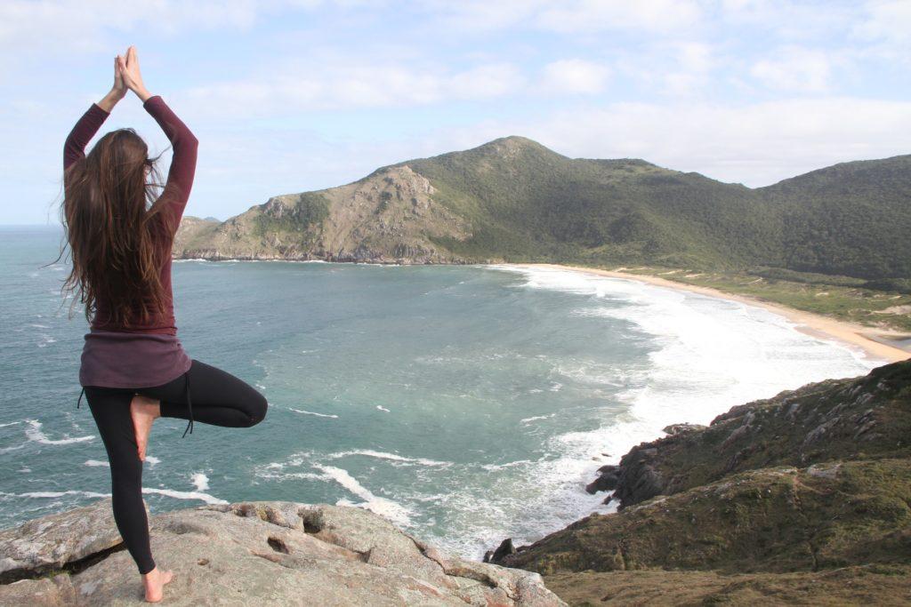 Frau macht Yoga am Meer